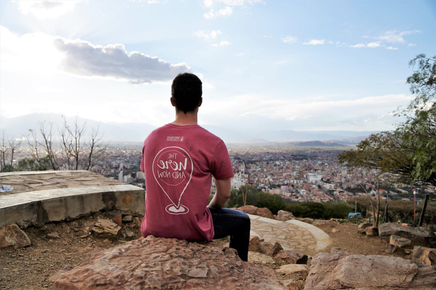 student sitting on a cliff looking at a city in the distance.
