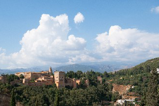 A scenic view of Spain with trees, rooftops and white clouds in the sky above the city.